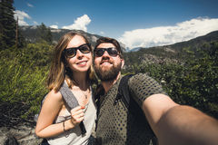 Happy smiling couple of students in love take selfie self-portrait while hiking in Yosemite National Park, California. Happy smiling couple in love take selfie Royalty Free Stock Images