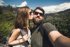 Happy smiling couple of students in love take selfie self-portrait while hiking in Yosemite National Park, California. Happy smiling couple in love take selfie Stock Image