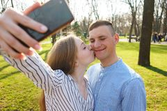 Happy smiling couple taking selfie, kiss and take pictures on sm stock image