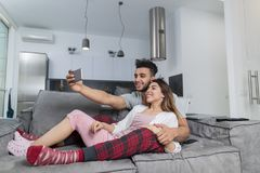Happy Smiling Couple Taking Selfie Photo On Cell Smart Phones Sitting On Couch In Modern Apartment, Young Man And Woman royalty free stock photo