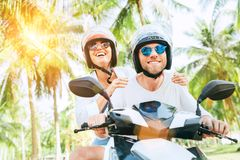 Happy smiling couple travelers riding motorbike scooter in safety helmets during tropical vacation under palm trees stock image