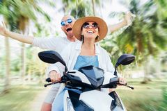 Happy smiling couple travelers riding motorbike scooter under palm trees. Tropical vacation  concept image royalty free stock photos