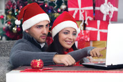 Happy smiling couple using a laptop at home in Christmas Royalty Free Stock Photography
