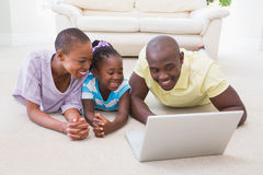 Happy smiling couple using laptop with their daughter Stock Images