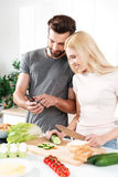 Happy smiling couple using mobile phone to find a recipe Royalty Free Stock Images