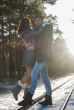 Happy smiling couple in winter park with beautiful sun rays. Stock Image