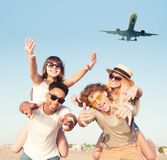 Happy smiling couples playing at the beach with aircraft in the sky stock images