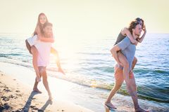 Happy smiling couples playing at the beach stock photography