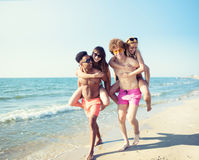Happy smiling couples playing at the beach royalty free stock photography