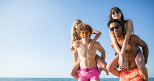Happy smiling couples playing at the beach royalty free stock photos