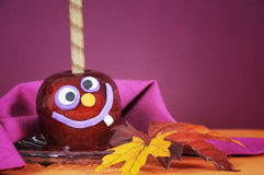 Happy smiling crazy face red toffee apple candy for trick or treat Halloween closeup. Happy smiling crazy face red toffee apple candy for trick or treat Royalty Free Stock Photo