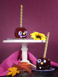 Happy smiling crazy face red toffee apples candy on stand for trick or treat Halloween. Food against a bright dark pink red and orange background, vertical Royalty Free Stock Photo