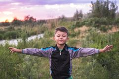 Happy smiling cute boy with eyes closed enjoying on a beautiful summer nature background.  royalty free stock photos