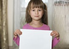 Happy smiling cute child girl holding white copy space sheet of drawing paper. Art education, creativity, advertisement concept.  royalty free stock image