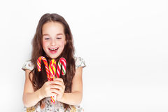 Happy, smiling cute little girl eating cristmas candy cane. Posing against a white wall. Stock Photo