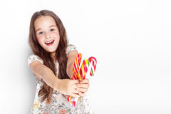 Happy, smiling cute little girl eating cristmas candy cane. Posing against a white wall. Royalty Free Stock Image