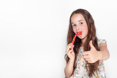 Happy, smiling cute little girl eating cristmas candy cane. Saying Ok. Posing against a white wall. Royalty Free Stock Photo