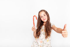Happy, smiling cute little girl eating cristmas candy cane. Saying Ok. Posing against a white wall. Stock Images