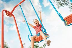 Happy smiling cute little girl have fun when swing on swing stock photography