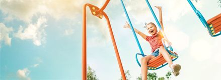 Happy smiling cute little girl have fun when swing on swing royalty free stock image