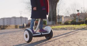 Happy smiling daughter child girl wearing safety helmet portrait riding segway at city park.Childhood,active,safety stock video footage