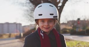 Happy smiling daughter child girl wearing safety helmet riding bicycle portrait at city park.Childhood,active,safety stock video