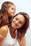 Happy smiling daughter hugging beautiful mother. Close-up portrait of happy smiling daughter hugging beautiful mother Stock Photo