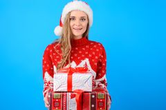 Happy smiling delightful lovely young woman in santa hat knitted royalty free stock photography