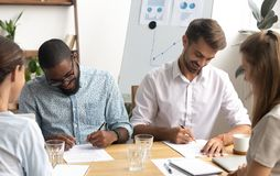 Happy smiling diverse businessmen putting signature on paper document. Sitting at table front of two caucasian business partners in office. Successful stock photos