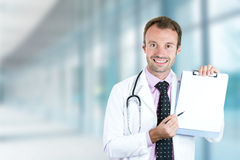 Happy smiling doctor with clipboard standing in hospital hallway royalty free stock images