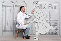 Happy smiling doctor examining superman. Everyone is a hero. Delighted handsome man smiling and examining Superman while sitting chair royalty free stock photography