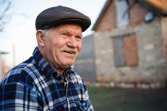 Free Happy Smiling Elder Senior Man Portrait With A Mustache In A Cap On The Background Of A Brick House In A Russian Village Royalty Free Stock Photography - 139758657