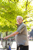happy and smiling elderly man with bike Royalty Free Stock Images