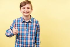 Happy smiling enthusiastic boy showing thumb up stock photo