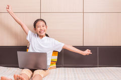 Happy smiling and excited asian girl using computer laptop noteb Royalty Free Stock Image
