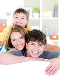 Happy smiling faces of young family. Close-up happy smiling faces of young family of three people with son - indoors Royalty Free Stock Photography