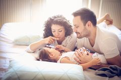 Cheerfully family together in bed. Happy smiling family in bed. Playful family at home together Royalty Free Stock Images