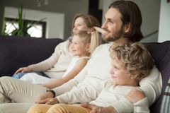 Happy smiling family with children sitting on sofa watching tv. Happy family with children sitting on sofa watching tv, young parents embracing son daughter Royalty Free Stock Photo