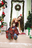 Happy smiling family on Christmas at house with gifts, young mother and little son in Santas red hat, lifestyle holiday Stock Photo