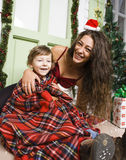 Happy smiling family on Christmas at house with gifts, young mother and little son in Santas red hat, lifestyle holiday Royalty Free Stock Photos