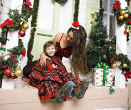 Happy smiling family on Christmas at house with gifts, young mother and little son in Santas red hat, lifestyle holiday Stock Photography