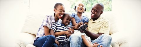 Happy smiling family on couch. In living room at home stock images