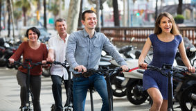 Happy smiling family of four with electrkc bikes Stock Photography