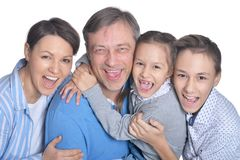 Happy smiling family of four posing on white background royalty free stock photography
