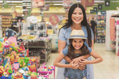 Happy smiling family having fun in store. Cheerful mother is hugging joyful daughter. They standing near toy department and looking at camera with wide smile Stock Photo