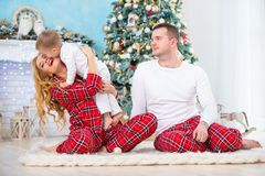 Happy Smiling Family In Checkered Pajamas Near The Christmas Tree And New Year`s Fireplace Stock Images