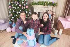 Happy smiling family with little child with gifts and christmas stock photos