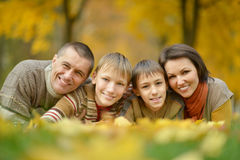 Family in autumn forest. Happy smiling family lying on leaves in autumn forest Stock Image