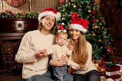 Happy smiling family near the Christmas tree celebrate New Year. Stock Photo