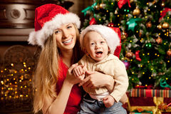 Happy smiling family near the Christmas tree celebrate New Year. Stock Photography